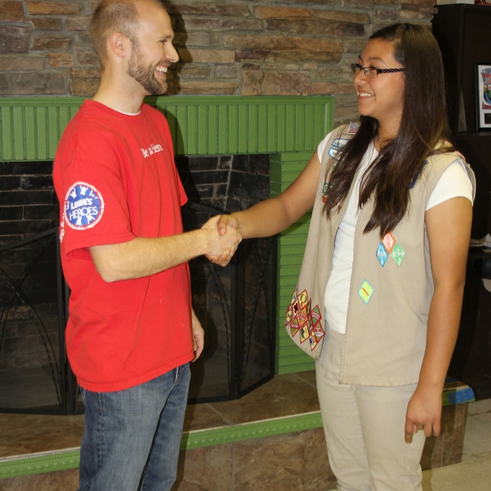 Ashley Villatoro, representing Maggie Ramirze, shaking hands with Hero Chris.
