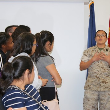 A group listens to a member of the Dental Battalion speak.